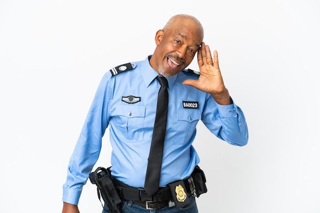 Giovane poliziotto isolato su sfondo bianco ascoltando qualcosa mettendo la mano sull'orecchio