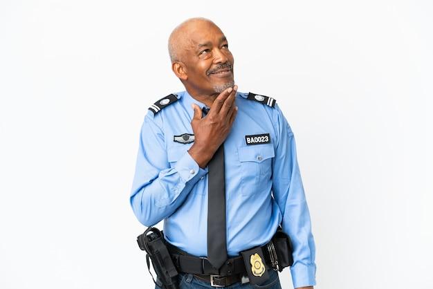 Giovane poliziotto isolato su sfondo bianco alzando lo sguardo mentre sorride