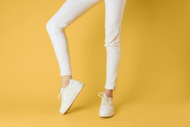 Giovane in posa con scarpe da ginnastica bianche alla moda