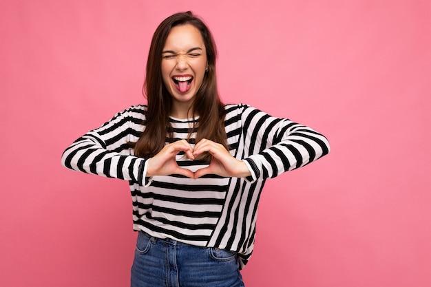Giovane bella donna castana felice adorabile positiva con emozioni sincere che indossano strisce casuali