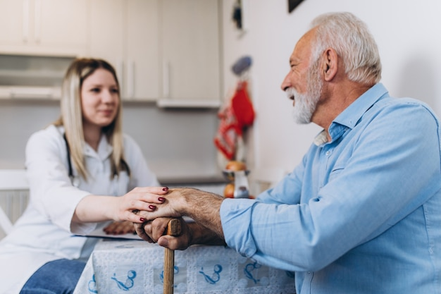 Giovane badante positivo che si prende cura di un uomo anziano in casa di cura.