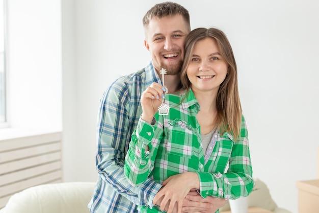 Giovani coppie positive che tengono le chiavi di un nuovo appartamento stando in piedi nel loro salotto