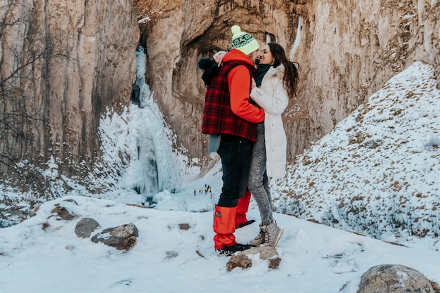 La giovane coppia positiva marito e moglie sono felici durante un viaggio invernale. amanti in montagna.
