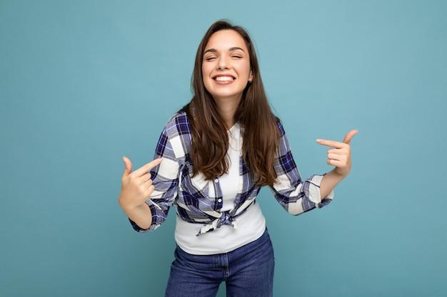Giovane bella donna castana sorridente deliziosa e positiva con emozioni sincere che indossa una camicia a quadri alla moda
