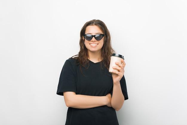 Una giovane ragazza positiva che beve caffè sorride alla telecamera con gli occhiali da sole addosso