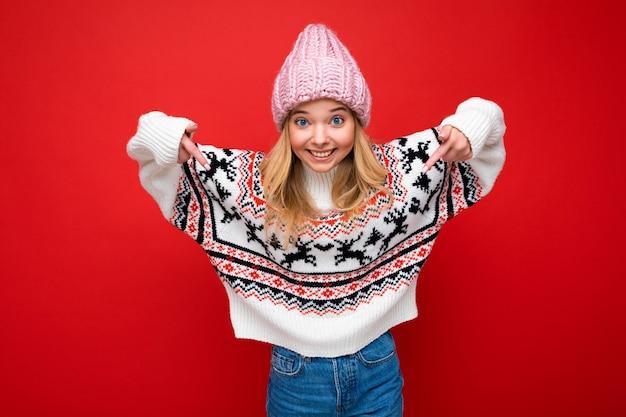 Giovane donna bionda attraente felice positiva con emozioni sincere che indossa il cappello lavorato a maglia rosa