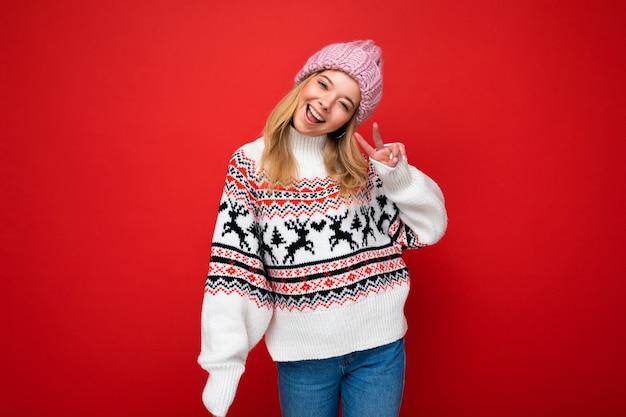 Giovane bella donna bionda felice positiva con emozioni sincere che indossa il cappello lavorato a maglia rosa
