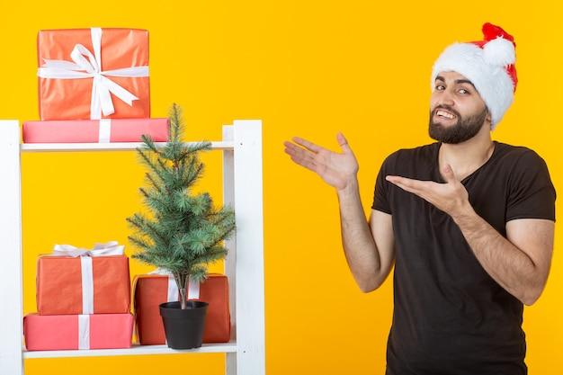 Giovane uomo positivo con la barba e il cappello di babbo natale è in piedi vicino alla cabina con regali e albero di natale sulla parete gialla. concetto di regalo di congratulazioni e sconti per natale