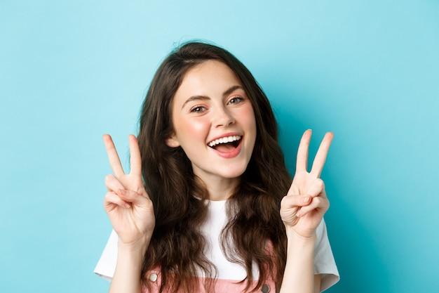 Giovane ragazza moderna positiva che invia solo buone vibrazioni, mostrando il segno v e sorridendo felice, in piedi su sfondo blu.