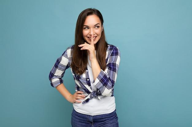Giovane bella donna sorridente positiva del brunet con emozioni sincere che indossa la camicia di controllo alla moda in piedi isolato sull'azzurro