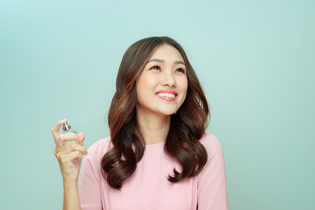 Giovane donna positiva che tiene in mano una bottiglia di profumo e la applica
