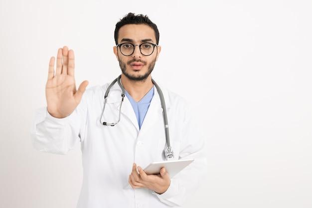 Giovane professionista in whitecoat e occhiali da vista che mostra un segnale di avvertimento a mano mentre ti guarda in isolamento