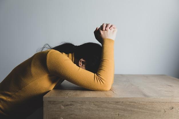Giovane donna di preghiera in camera oscura