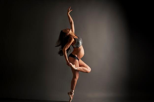 Giovane ballerina incinta che esegue posa di balletto classico con top in paillettes e biancheria intima nera in studio