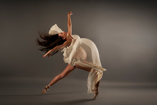 Giovane ballerina incinta che esegue posa di balletto classico con un panno di seta