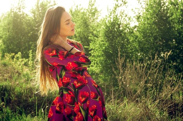 Giovane ragazza incinta in abito in natura