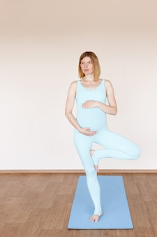 Una giovane ragazza incinta in una tuta sportiva si erge su una gamba in un'asana. yoga per donne incinte