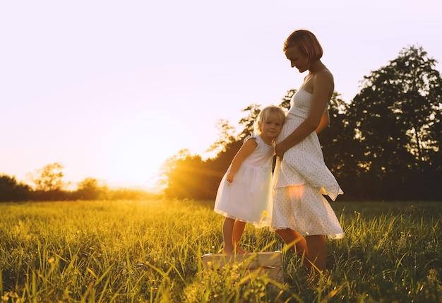 Giovane madre incinta e figlia in abito sulla natura all'aperto donna incinta e bambino in prato