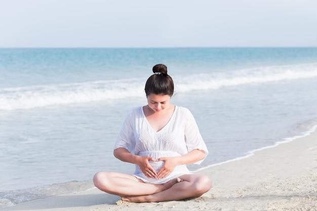 Giovane donna incinta sulla spiaggia vicino al mare blu e respirazione