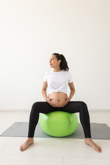 Una giovane donna incinta che fa esercizio di rilassamento usando una palla fitness mentre è seduta su un tappetino