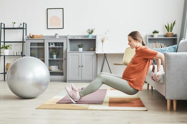 Giovane donna incinta che fa esercizi sportivi nel soggiorno di casa