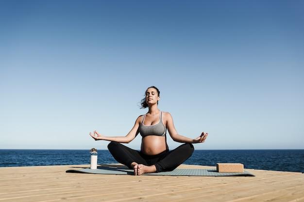 Giovane donna incinta che fa meditazione yoga all'aperto