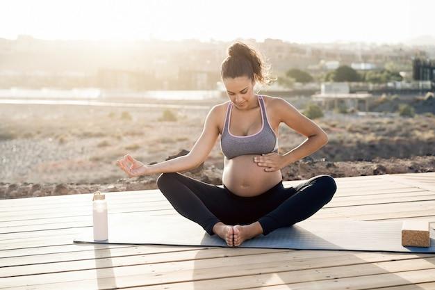 Giovane donna incinta che fa yoga all'aperto - focus sulla mano destra che tiene la pancia