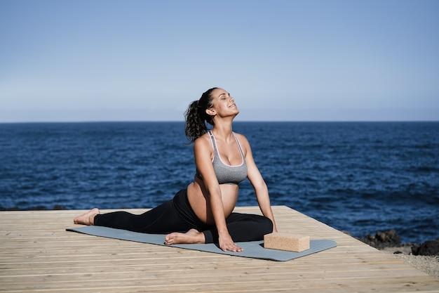 Giovane donna incinta che fa yoga all'aperto con la spiaggia sullo sfondo - focus sul viso
