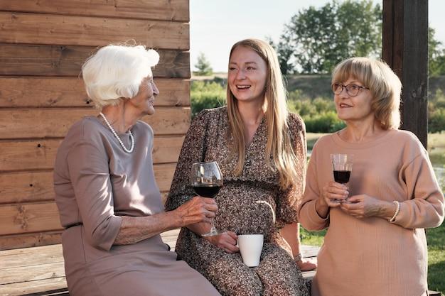 Giovane donna incinta, bere il tè e parlare con due donne anziane con bicchieri di vino rosso che riposano all'aperto