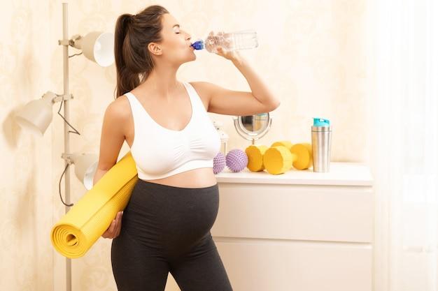 Giovane donna incinta durante il suo allenamento fitness a casa