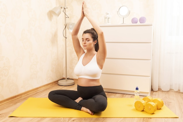 Giovane donna incinta durante il suo allenamento di yoga a casa