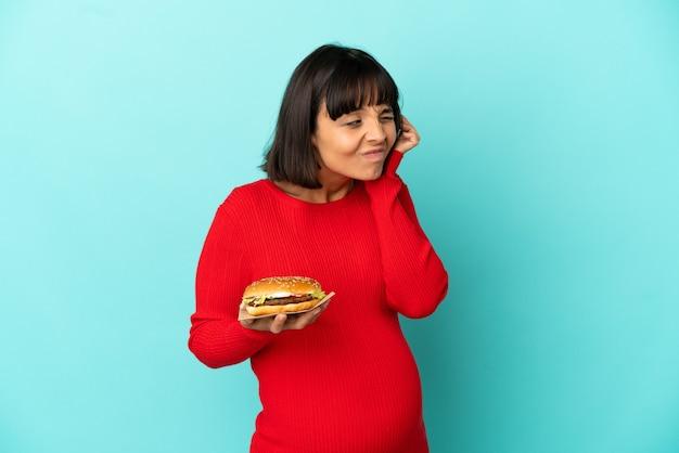 Giovane donna incinta tenendo un hamburger su sfondo isolato frustrato e coprendo le orecchie