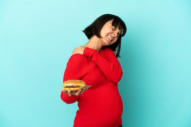 Giovane donna incinta tenendo un hamburger su sfondo isolato che soffre di dolore alla spalla per aver fatto uno sforzo