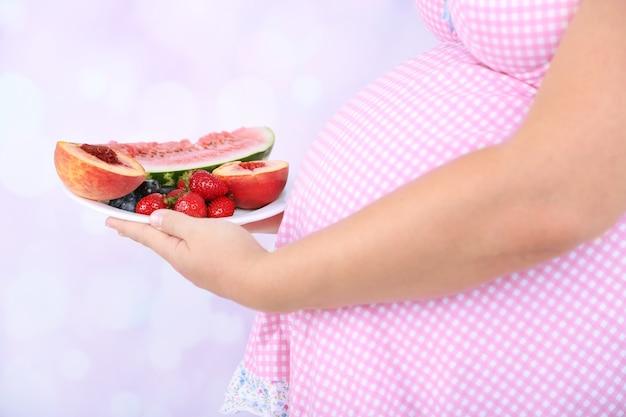 Piatto della tenuta della giovane donna incinta con i frutti sulla superficie luminosa