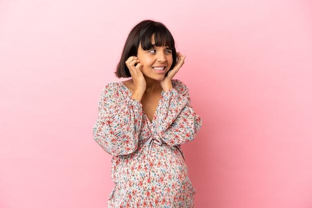 Giovane donna incinta su sfondo rosa isolato frustrata e che copre le orecchie