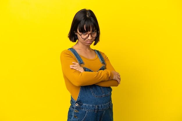 Giovane donna incinta su sfondo giallo isolato sentirsi sconvolta