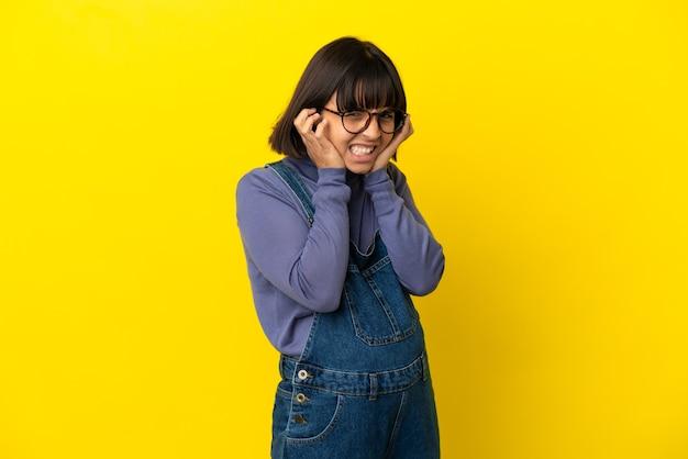 Giovane donna incinta su sfondo giallo isolato frustrata e che copre le orecchie