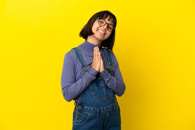La giovane donna incinta sopra fondo giallo isolato tiene insieme il palmo. la persona chiede qualcosa
