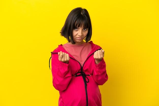 Giovane donna incinta su sfondo giallo isolato che fa un gesto di denaro ma è rovinata