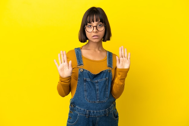 Giovane donna incinta su sfondo giallo isolato facendo gesto di arresto e deluso