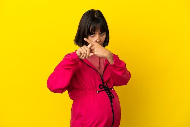 Giovane donna incinta su sfondo giallo isolato facendo un gesto di arresto con la mano per fermare un atto