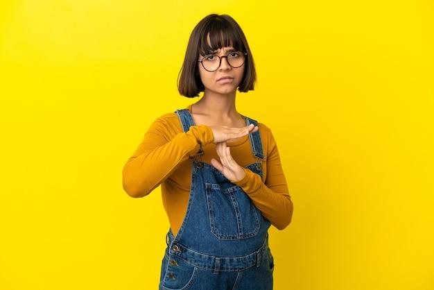 Giovane donna incinta su sfondo giallo isolato che fa gesto di time out