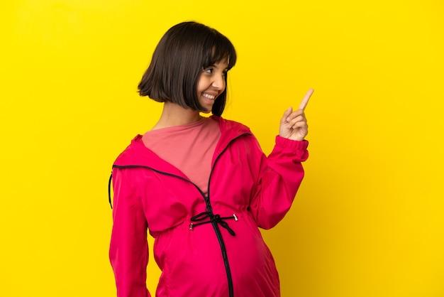 Giovane donna incinta su sfondo giallo isolato che punta verso l'alto una grande idea