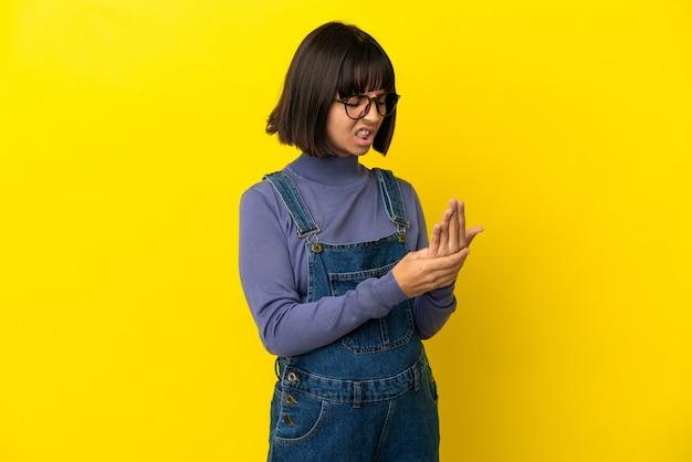 Giovane donna incinta su sfondo giallo isolato che soffre di dolore alle mani