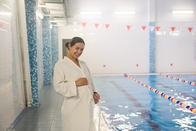 Giovane donna incinta vicino alla piscina.