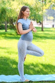 Giovane donna incinta che pratica yoga all'aperto