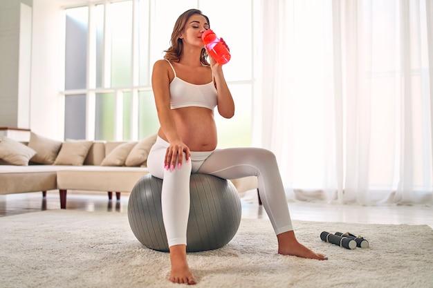 La giovane donna incinta in abiti sportivi fa esercizi e beve acqua mentre è seduta su una palla fitness. sport e uno stile di vita sano durante la gravidanza.