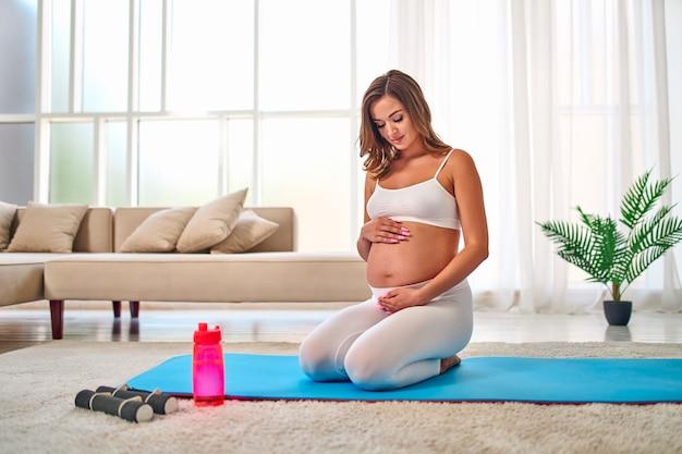 Giovane donna incinta in abiti sportivi facendo esercizi su un tappetino di gomma in soggiorno. nelle vicinanze ci sono manubri e una bottiglia d'acqua. sport e uno stile di vita sano durante la gravidanza.
