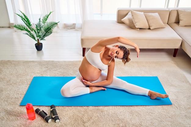 La giovane donna incinta in abiti sportivi che si siede sulla stuoia fa gli esercizi. nelle vicinanze ci sono manubri e una bottiglia d'acqua. sport e uno stile di vita sano durante la gravidanza.