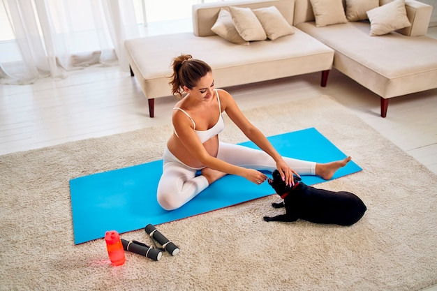 La giovane donna incinta in abiti sportivi seduta sul tappeto sta facendo esercizi con il suo cane. nelle vicinanze ci sono manubri e una bottiglia d'acqua. sport e uno stile di vita sano durante la gravidanza.
